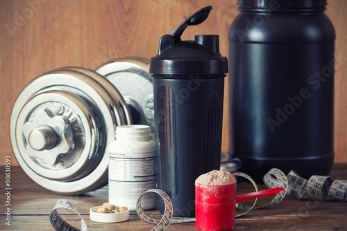 Fotografia  Whey protein powder in scoop with vitamins and plastic shaker