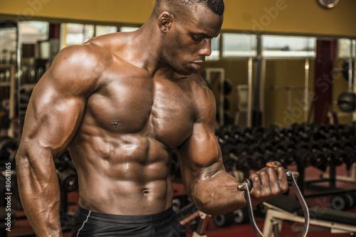 Fotografie, Obraz  Hunky muscular black bodybuilder working out in gym