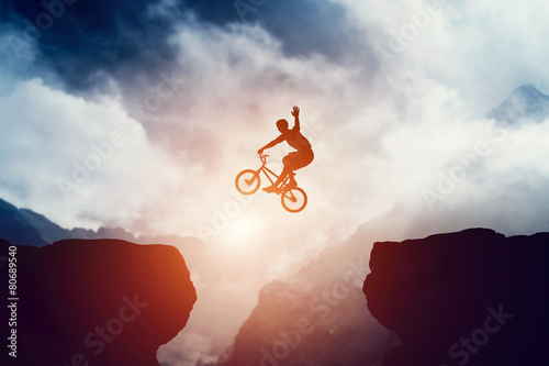 Man jumping on bmx bike over precipice in mountains at sunset.