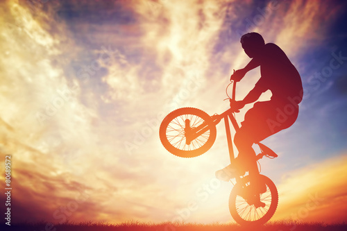 Man riding a bmx bike performing a trick against sunset sky