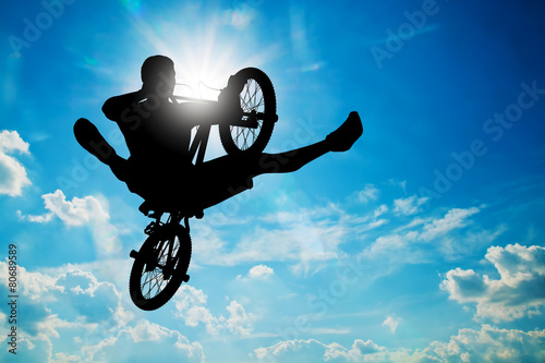 Man jumping on bmx bike performing a trick against sunny sky