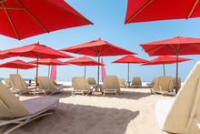 Beach Chairs And Umbrellas On A Sand Beach