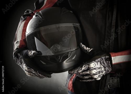 Motorcyclist with helmet in his hands. Dark background Canvas-taulu