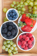 fresh berries in bowl and green grapes on wooden tray, vertical