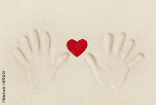 Zwei Hände im Sand halten ein rotes Herz - kaufen Sie