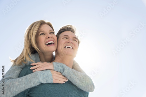 Man Giving Piggyback Ride To Woman Against Clear Sky Fototapet