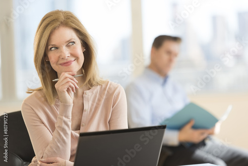 Fototapety, obrazy: Thoughtful Businesswoman Smiling In Office