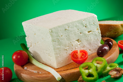 Fotografie, Obraz  White feta cheese on wooden board and green background