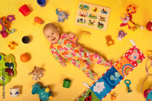 Smiling baby with toys on a yellow ground #80827747