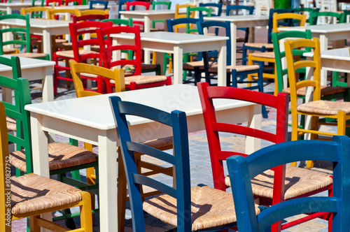 Multicolored greek chairs in the outdoor cafe #80827752