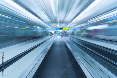 Blurred movement along airport walkway #80827772