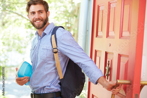 Young Man Leaving Home For Work With Packed Lunch Fotobehang