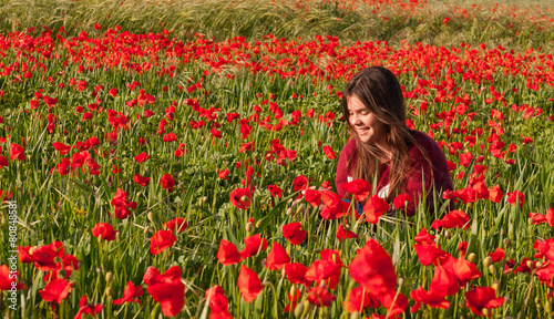 Happy smiling teenage girl sitting in a red poppy field Wallpaper Mural
