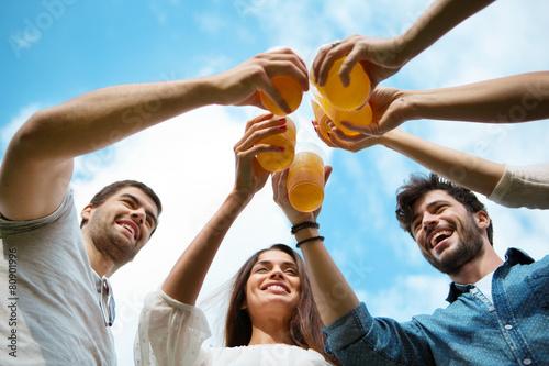 Fotografie, Tablou  Vier Freunde mit Plastikbechern stoßen gemeisam an