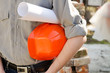 Man holds a protective construction helmet and the project in h