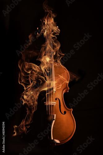 Fotografia violin on fire over black bg
