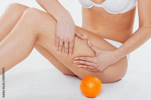 Láminas  Beautiful female body with orange on a white background