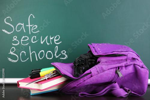 Valokuva  Gun in school backpack on wooden desk, on blackboard background