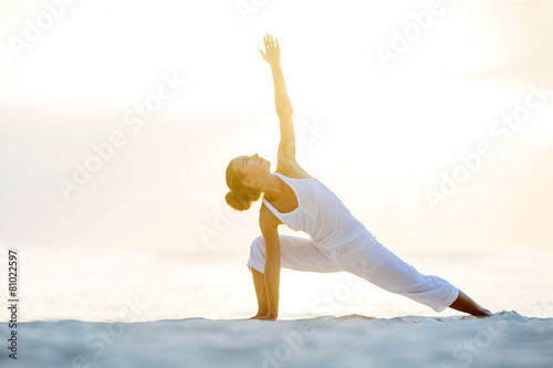 Fényképezés  Caucasian woman practicing yoga at seashore