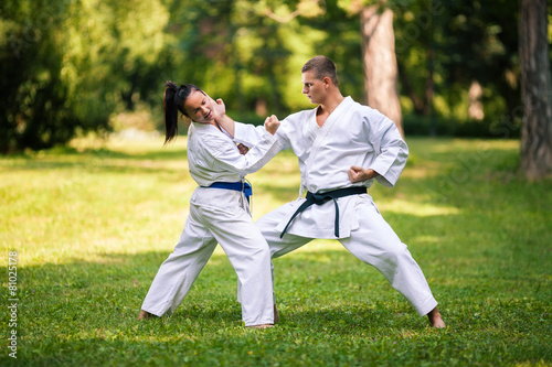 Staande foto Vechtsport Two young people practicing karate in a park