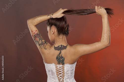 Plakat widok z tyłu całkiem młoda kobieta z tatuażami pozowanie w gorset