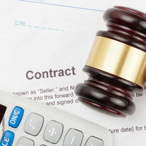 Gavel and calculator over contract and financial documents
