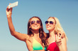two smiling women making selfie on beach