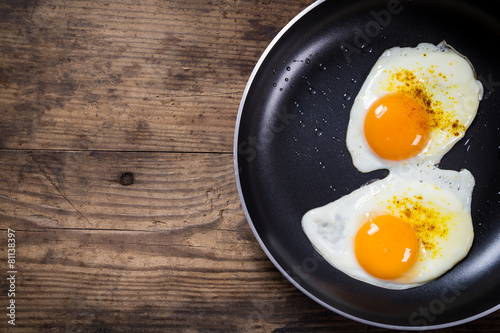 Spoed Foto op Canvas Gebakken Eieren two frying eggs in pan on table