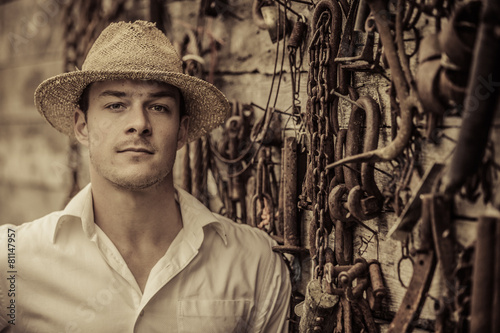Fotografía  Farmer Portrait in front of a Wall Full of Tools
