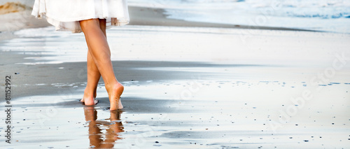 Woman walking on sand beach Wallpaper Mural