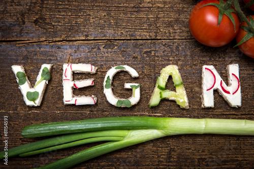 Fotografie, Obraz  Wort Vegan aus verschieden belegten Broten auf Holztisch