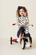 Girl In Spots On Tricycle