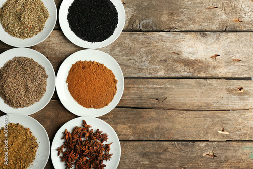 Papiers peints Herbe, epice 2 Different spices on plates, on old wooden table