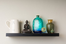 Wall Shelf Featuring Pottery And A Buddha