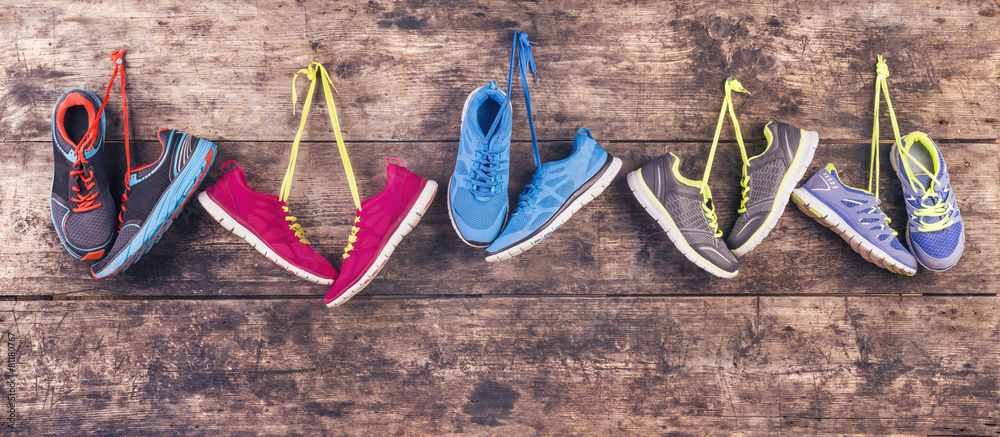 Fototapeta Sports shoes hang on a nail on a wooden fence background