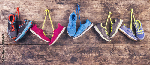 Sports shoes hang on a nail on a wooden fence background Wallpaper Mural