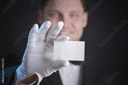 Photo butler wearing white gloves and holding a business card