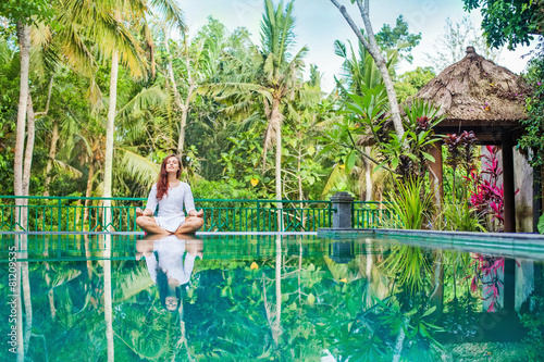Woman meditation at gorgeous pool side of luxury tropical villa Wallpaper Mural