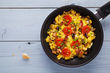 Scrambled Eggs In A Pan With Bacon, Onion And Tomatoes Sprinkled