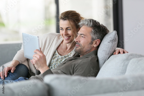 Mature couple using digital tablet relaxing in sofa Poster Mural XXL