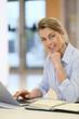 Businesswoman working in office on laptop