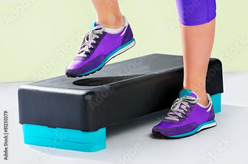 Fotografie, Obraz  Female feet in violet sneakers on fitness step.