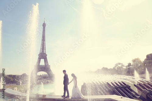 Bride and groom having fun at fountain in Paris Poster
