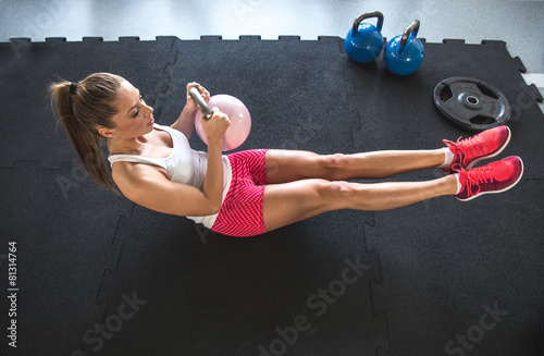Woman working on her abs with kettlebell Fotobehang