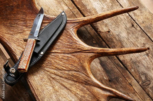Foto op Canvas Jacht Moose antler with hunting knives on wooden background