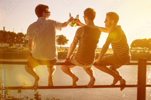 Fotografía  Tres amigos que beben la cerveza