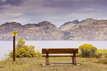 Wooden Park Bench And Warning Sign Overlooking Lake