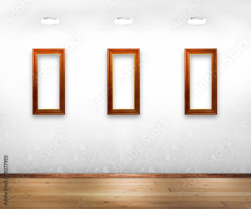 Three wooden frames on white wall. - Buy this stock photo and ...