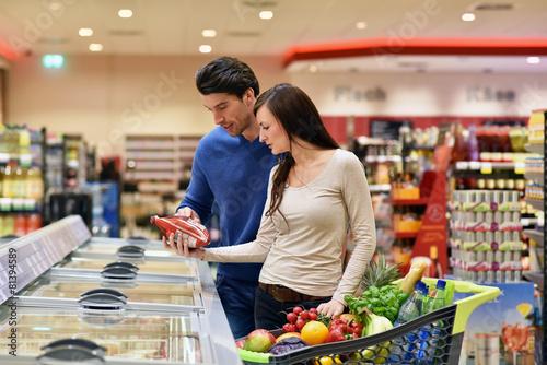 Junge Paar in einem Supermarkt einkaufen Fototapete