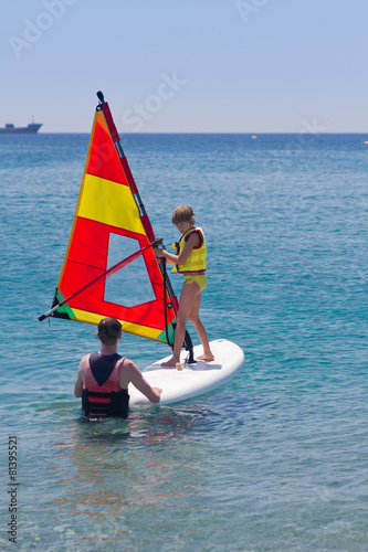 Little girl taking a lesson of windsurfing on a calm sea. Instructor and student or father and daugher. Learning new skills at young age